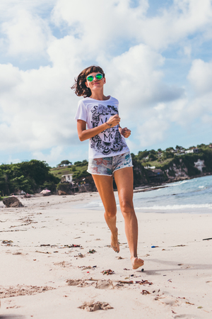 Sporty and healthy young woman in sunglasses running on the tropical beach during sunset. Bali island, Indonesia.