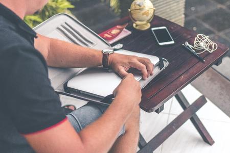 Man with luxury snakeskin python laptop case on a table outside the asian garden. Men fashion concept. Laptop bag.