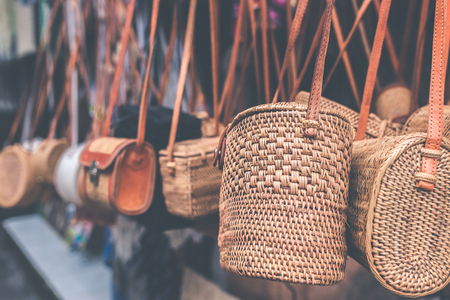 Rattan handbags hanging in the outdoor local asian store. Bali island. Фото со стока