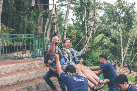 BALI, INDONESIA - JANUARY 23, 2018: Couple swings in the deep jungle of Bali island.