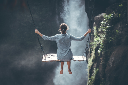 Beautiful woman swings near waterfall in the jungle of Bali island, Indonesia.