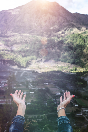 Woman hands on mountain background. Volcano Batur. Bali island.