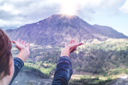 Woman hands on mountain background. Volcano Batur. Bali island.