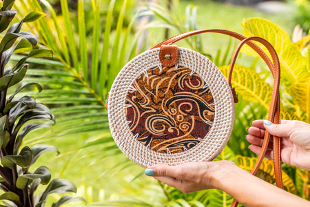 Fashionable stylish rattan bag in the tropical garden. Tropical island of Bali, Indonesia. Rattan handbag.