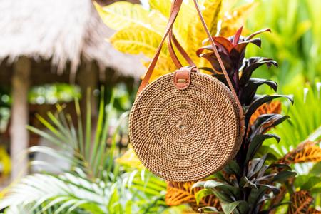 Fashionable stylish rattan bag in the tropical garden.