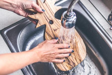 Planche à découper en bois de teck à laver. Femme mains laver planche à découper en teck.