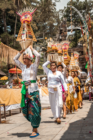 BALI, INDONESIA - SEPTEMBER 25, 2018: Balinese women in traditional clothes on a big ceremony in famous Tirta Empul Temple. Stock Photo - 119934882