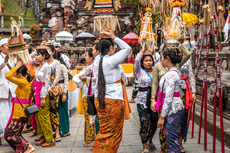 BALI, INDONESIA - SEPTEMBER 25, 2018: Balinese women in traditional clothes on a big ceremony in famous Tirta Empul Temple. Stock Photo - 119934911