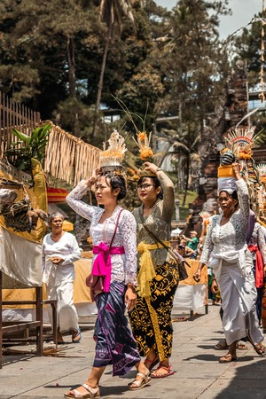 BALI, INDONESIA - SEPTEMBER 25, 2018: Balinese women in traditional clothes on a big ceremony in famous Tirta Empul Temple. Stock Photo - 119934919