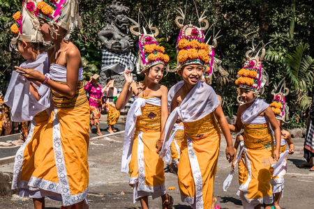BALI, INDONESIA - SEPTEMBER 25, 2018: Balinese children in traditional clothes on a big ceremony in Tirta Empul Temple. Stock Photo - 119934952