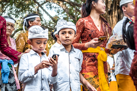 BALI, INDONESIA - SEPTEMBER 25, 2018: Balinese children in traditional clothes on a big ceremony in Tirta Empul Temple. Stock Photo - 119934963