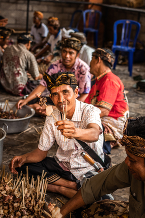 BALI, INDONESIA - SEPTEMBER 25, 2018: Men preparing for cooking traditional balinese food in a famous Tirta Empul Temple. Editorial