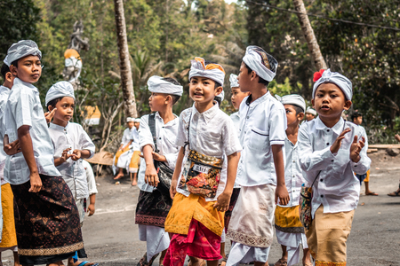 BALI, INDONESIA - SEPTEMBER 25, 2018: Balinese children in traditional clothes on a big ceremony in Tirta Empul Temple.