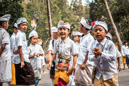 BALI, INDONESIA - SEPTEMBER 25, 2018: Balinese children in traditional clothes on a big ceremony in Tirta Empul Temple. Stock Photo - 119934989