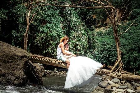 Young honeymoon newleds couple on a mountain river. Bali island.