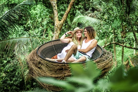 Traveler honeymoon couple in decorative nest the jungle of Bali island, Indonesia. Couple in the rainforest. Stockfoto