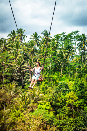 Young tourist man with long hair swinging on the cliff in the jungle rainforest of a tropical Bali island. Imagens