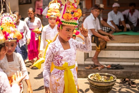 BALI, INDONESIA - OCTOBER 3, 2018: Balinese girls in traditional costume on a balinese family ceremony in desa Pejeng Kangi. Stock Photo - 119935096