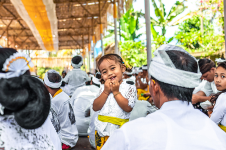 BALI, INDONESIA - OCTOBER 9, 2018: Small girl on a balinese traditional ceremony. Bali island. Stock Photo - 119935254