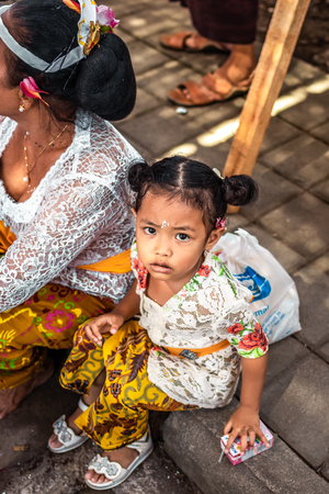BALI, INDONESIA - OCTOBER 9, 2018: Small girl on a balinese traditional ceremony. Bali island.