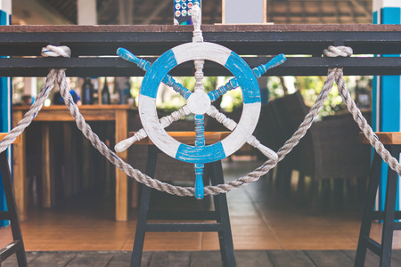 Wooden steering wheel in the beach restaurant. Bali island. Indonesia.