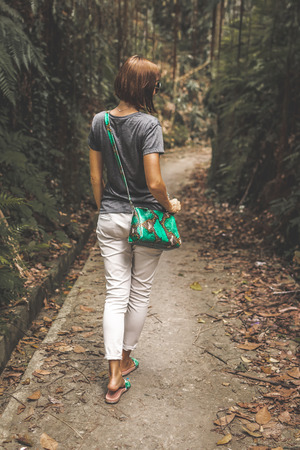 Woman with luxury snakeskin python handbag in the tropical forest. Bali island. Indonesia.
