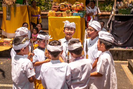BALI, INDONESIA - OCTOBER 3, 2018: Balinese boys ritual dance in traditional costume on a balinese family ceremony in desa Pejeng Kangi. Stock Photo - 119935315