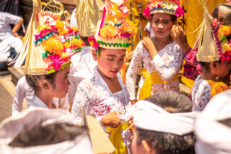 BALI, INDONESIA - OCTOBER 3, 2018: Balinese kids in traditional costume on a balinese family ceremony in desa Pejeng Kangi. Stock Photo - 119935328