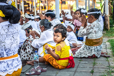 BALI, INDONESIA - OCTOBER 9, 2018: Small girl on a balinese traditional ceremony. Stock Photo - 119935370