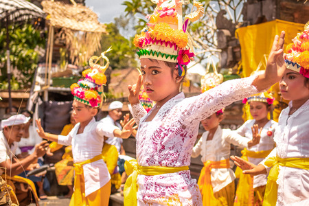 BALI, INDONESIA - OCTOBER 3, 2018: Balinese girls dancing in traditional costume on a balinese family ceremony in desa Pejeng Kangi. Stock Photo - 119935380