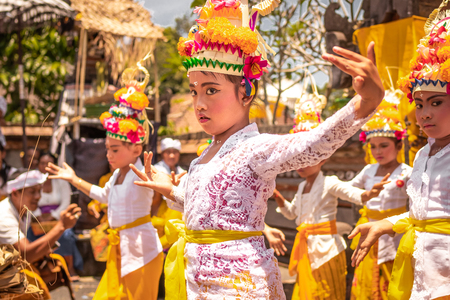BALI, INDONESIA - OCTOBER 3, 2018: Balinese girls dancing in traditional costume on a balinese family ceremony in desa Pejeng Kangi.