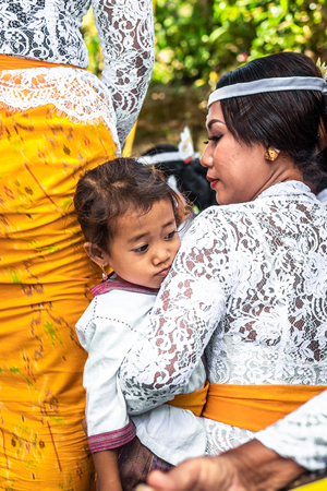 BALI, INDONESIA - OCTOBER 9, 2018: Small girl on a balinese traditional ceremony. Stock Photo - 119935395