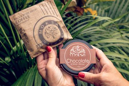 BALI, INDONESIA - DECEMBER 13, 2018:  Woman hands with natural balinese cosmetics on a green tropical background.
