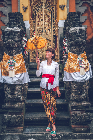 European young woman in balinese traditional temple. Bali island.