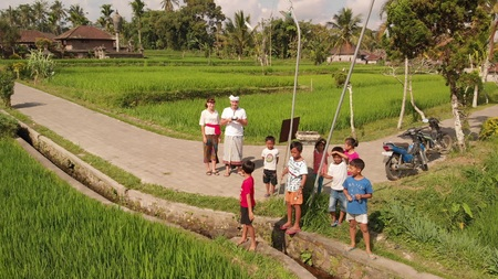 BALI, INDONESIA - SEPTEMBER 25, 2018: 4K aerial flying video of Balinese children with european tourist. 写真素材 - 119935561