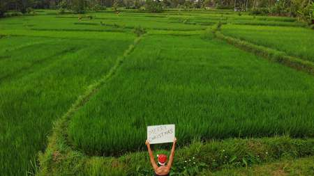 Young woman with red hat and whiteboard with handwritten text merry christmas on a tropical green background. XMas Greetings from Bali island, Asia.
