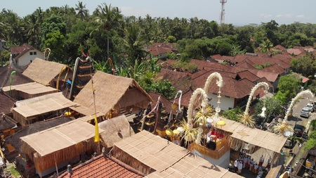 4K aerial flying video of balinese houses during the big celebration. Bali ceremony in village, Ubud. Roofs of balinese houses. Indonesia.