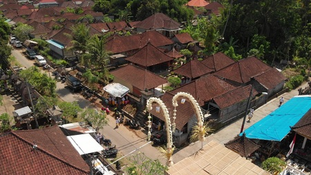 4K aerial flying video of balinese houses during the big celebration. Bali ceremony in village, Ubud. Roofs of balinese houses.