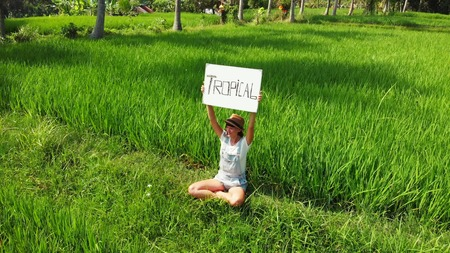 Young woman outdoors with whiteboard and handwriting word tropical on it. Drone flying footage. Green bright tropical background. Beautiful tropical travel concept. Bali island. 写真素材 - 116727267