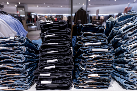 Stack of jeans in the store. Shopping mall. Shopping concept.