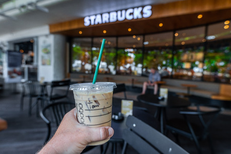 BALI, INDONESIA - FEBRAURY 19, 2019: Man hand with Iced latte in Starbucks. Shopping mall in Kuta, Beachwalk. Editorial
