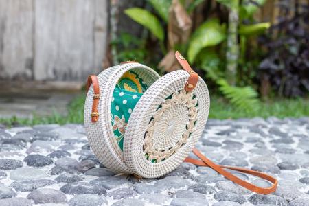 Fashion organic handmade rattan bag on a tropical background. Bali island.