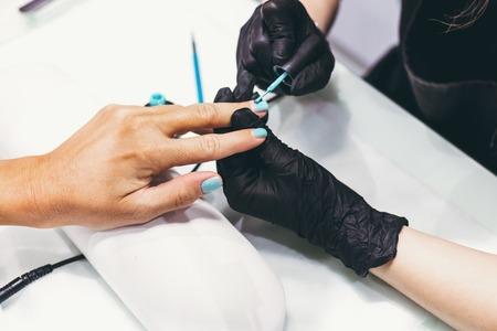 Master of manicure in work progress. Beauty salon. Hand treatment concept.