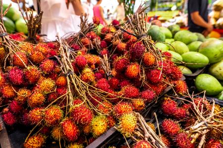Healthy fruits rambutans background, red Healthy fruits rambutans, rambutans in a supermarket local market of rambutans ready to eat, sweet Thai fruit. Stock Photo