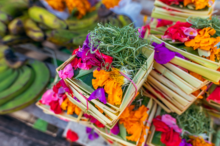 Traditional balinese handmade offering to gods on a morning market in Ubud. Bali island. Indonesia. Banco de Imagens