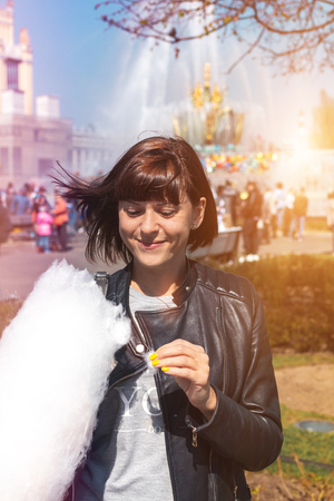 Close up portrait of a smiling excited girl holding cotton candy in the park close to fountain. Standard-Bild