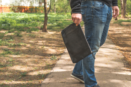Man with snakeskin python handbag on nature background. Stock Photo