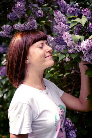 Beautiful woman in a spring garden with blooming lilacs. Nature background. Beauty.
