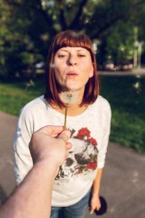 Girl blowing on white dandelion in the green park at summer time.