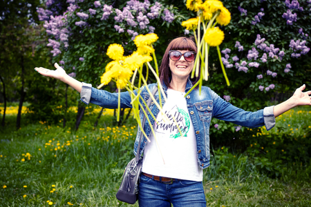 Woman with dandelions in a green spring park outdoors. Young female with yellow dandelions. Stock Photo - 124620544